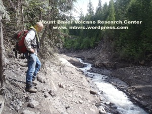 6-9-13: The river has cut a 10-m-deep canyon through the May 31 debris flow deposit.Dave is standing on the margin of the 5/31/13 deposit. Chris Magirl photo.