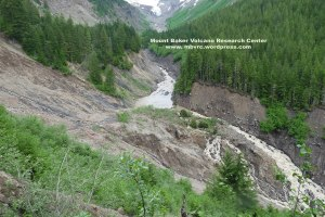 Lower landslide on June 29th from a similar perspective. Click to enlarge. Gravel bars are visible in the upstream end of the pond. Note enlarged river channel and new channel in center of the landslide toe.