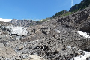 A 100-foot-high wall of 20th moraine rises at right above the glacier terminus. Ice peeks out of the landslide debris beneath.